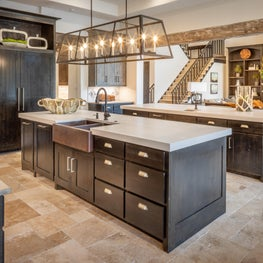 This kitchen with double islands has beautiful cabinetry and exposed beams
