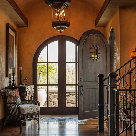 Foyer with textured walls, wrought iron stair banisters and rounded doors