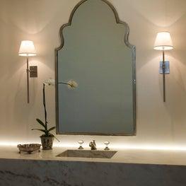 Floating vanity with elegant skinny sconces.