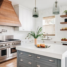 White kitchen with gray-green custom island, wood hood, Wolf range, wine fridge.