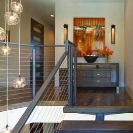Landing features cantilever console and bold art with view of cluster chandelier