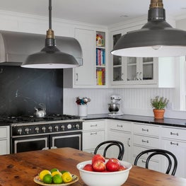 Black and white farmhouse kitchen with soapstone backsplash