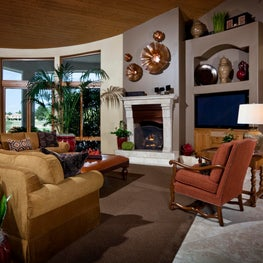 Comfortable family room in warm neutrals, red accents; stone & copper fireplace