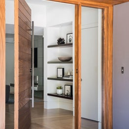 Front pivot door leads to an open floor plan in modern home in SF Bay Area.