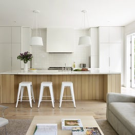 Bright, open kitchen with calacatta marble-topped island & concealed appliances