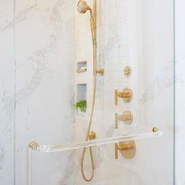 Caesarstone walls and gold Kohler rain-head fixtures add luxury.