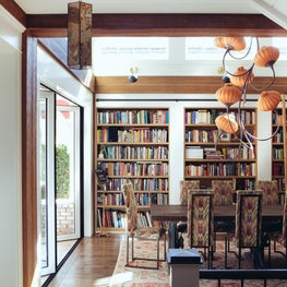Sustainable cottage dining room with statement chandelier and library wall