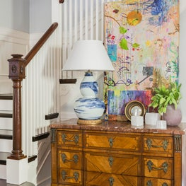 Colorful stairwell composition with statement table lamp modern art and antiques