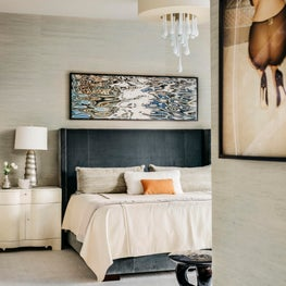 Grey bedroom with grasscloth walls and bold, contemporary art, blue velvet upholstered bed
