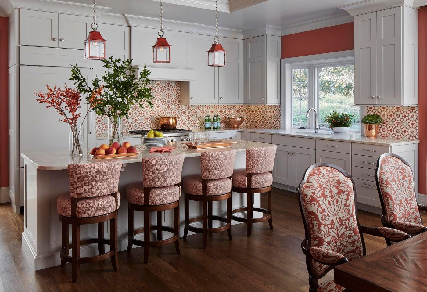 Gray, coral & orange kitchen area with red lantern pendants. Concrete splash