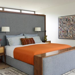 Contemporary bedroom with custom headboard that doubles as a built-in drawer unit and media center