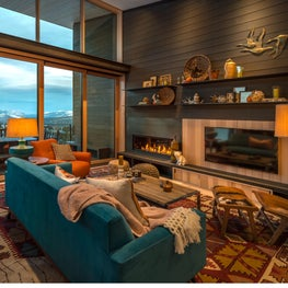 Mountain living room with fireplace and floor-to-ceiling window walls