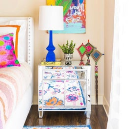 Mirrored nightstand with colorful rug and art