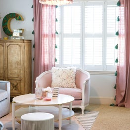 Bright master bedroom seating area with tasseled chandelier and curtains, pink antique style chair