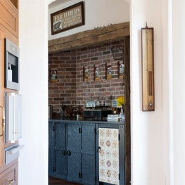 The old kitchen is now a  Butler's pantry with original cast-iron tiles.