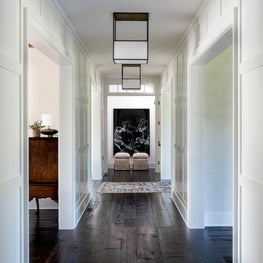 Hamptons Residence Entry Hall with paneled walls and dark wood floors.