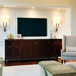 Custom media cabinet in paneled niche w/ flat-screen TV, sconces