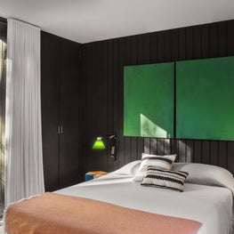Modern bedroom with black paneled walls, green accents, floor to ceiling window