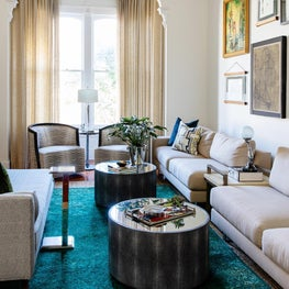 Eclectic Victorian living room with with a pop of teal and a salon wall of art collected by the homeowners.