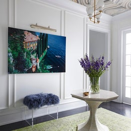 Gallery with custom print ceiling, wainscoting, and tulip pedestal table