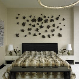 A master bedroom with a custom ceramic installation on the wall, a crystal chandelier overhead, and a blackened steel bench.