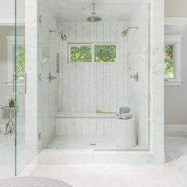 Custom shower with mosaic tile, custom glass enclosure, and double shower heads.