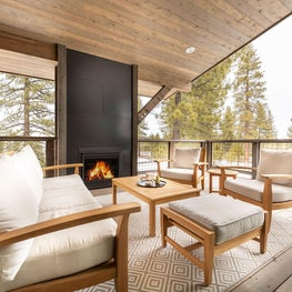 Deck sofa, chairs and coffee table with light wood and cushions, geometric outdoor rug, metal fireplace surround