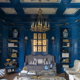 Rich blue-lacquered study with unexpected pops of gold and brass accessories