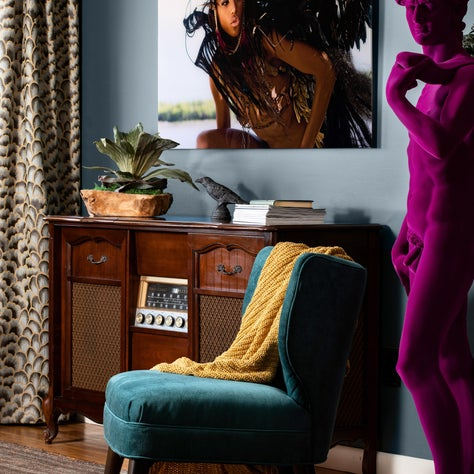 NYC apartment with dark walls and bold artwork, featuring a purple David statue!