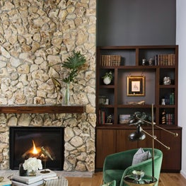 Stone fireplace in this renovated rustic home in horse country