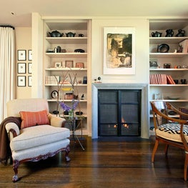 Living room with shelving built-in, fireplace, warm palette