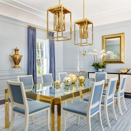 This blue dining room has gold accents, custom millwork and unique fixtures.