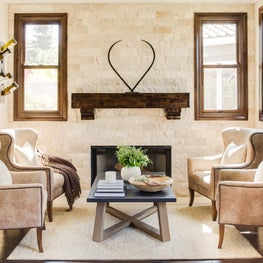 Stone walls; wood mantel; wing chairs equal a stunning wine tasting/game room.