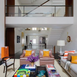 Double-high living room with contemporary furniture and open second-floor hallway