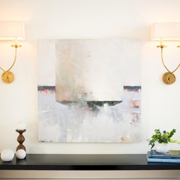Waterfall console table w/ brass sconces & modern art, design by Sophia Shibles