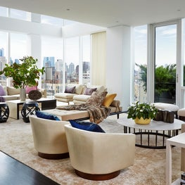 Dramatic double-height penthouse living room at The Lucida, with dark wood, chrome accents, and a muted palette
