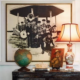 Jazzy entrance hall with a black and white second line brass band painting over another of a guitar player.