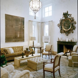 Double- high, neutral living room with geometric pendant and neutral seating