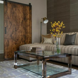 Sitting room with a refined take on a barn door and lucite coffee table