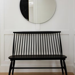 Chic black bench with round mirror in hallway