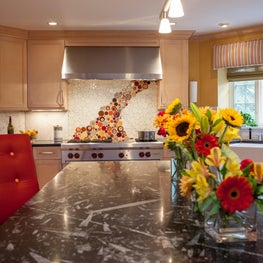 A waterfall of colors cascades down the backsplash in a transitional kitchen.