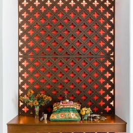Moroccan inspired entryway with floating wooden bench and artful screen backdrop