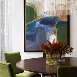 contemporary dining room with green chairs, brass and wood dining table, large colorful artwork, sheer drapery and brass chandelier