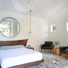 East Hampton Master Bedroom with Vintage Nakashima Headboard, McCabe Nightstands, Green Leather Wegner Armchairs