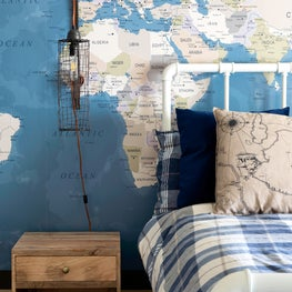 Stunning boys bedroom with a nautical lamp and a playful map wallcovering