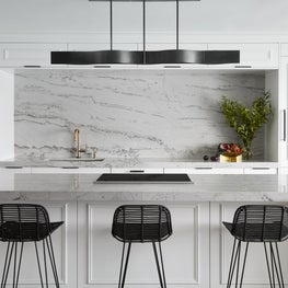 Custom white kitchen with full height quartzite backsplash and island with waterfall sides.