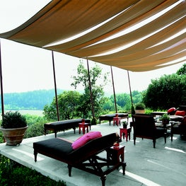 Cantilevered concrete with teak furnishings and awning overlooking the valley.
