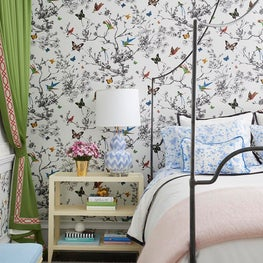 Bright bedroom with butterfly wallpaper, green curtains, black iron bed
