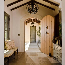 Rustic French entry hall with arched wood door, stone floor, and iron chandelier