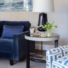 Blue velvet sofa with leather wrapped glass side table